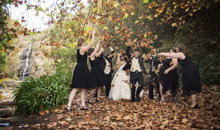 Bridal party throwing leaves