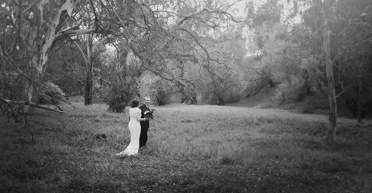 Bride and groom walking through grass