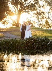 Bride and groom above pond