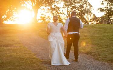 Bride and groom walking towards sunset