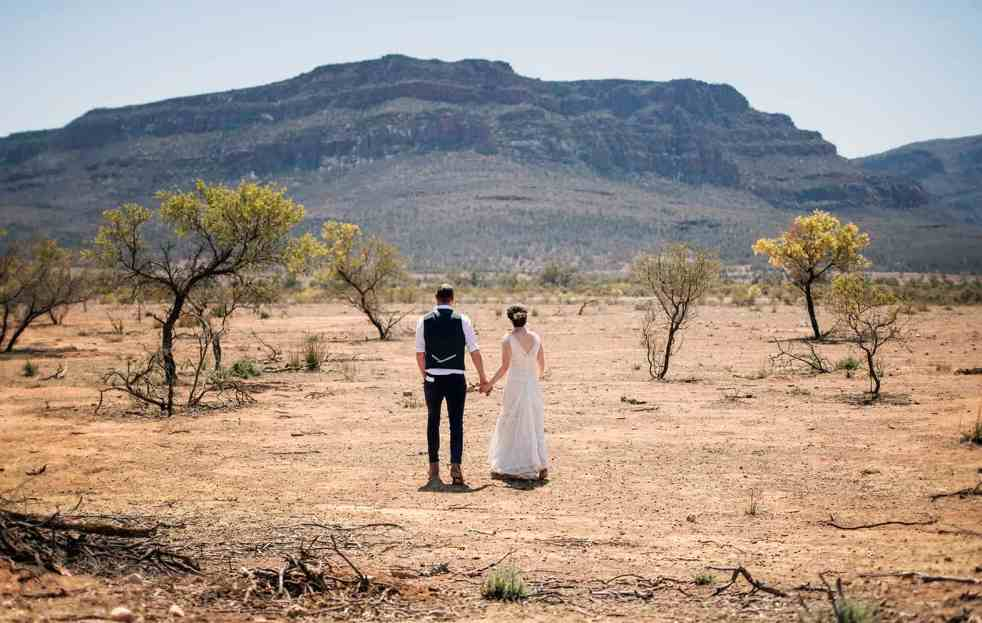 Bride and groom walking towards Wilpena Pound