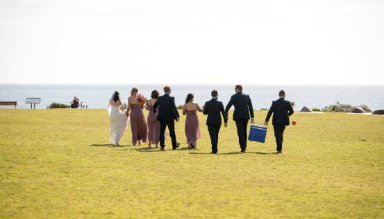 Bridal party walking to beach