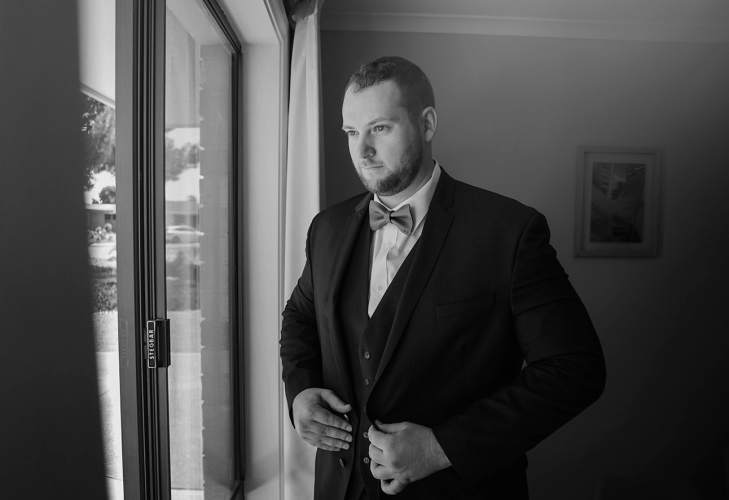 Groom getting ready by window