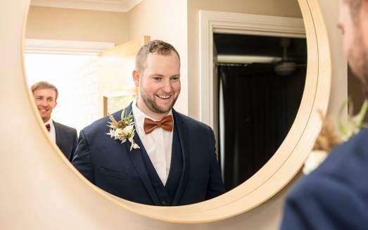 Groom smiling in mirror