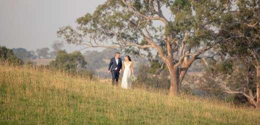 Bride and groom walking through paddock