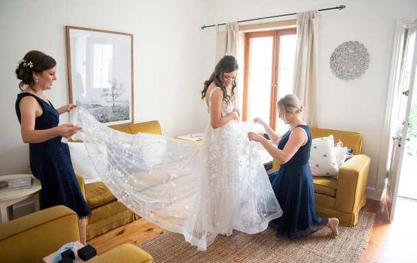 Bridesmaids helping put on dress
