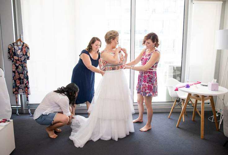 Girls helping put ont he wedding dress