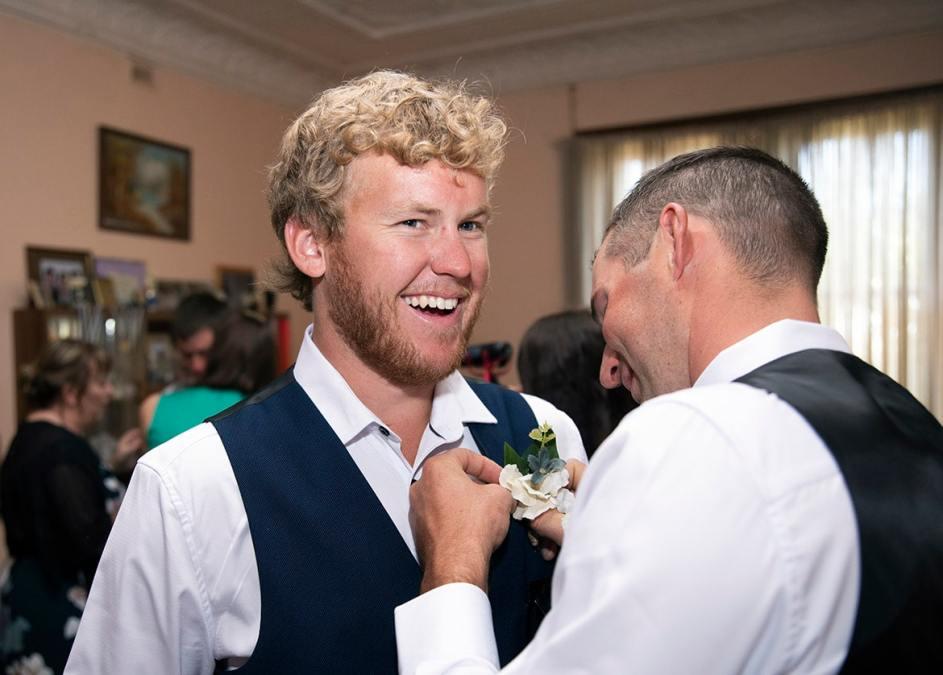 groomsman putting on tie