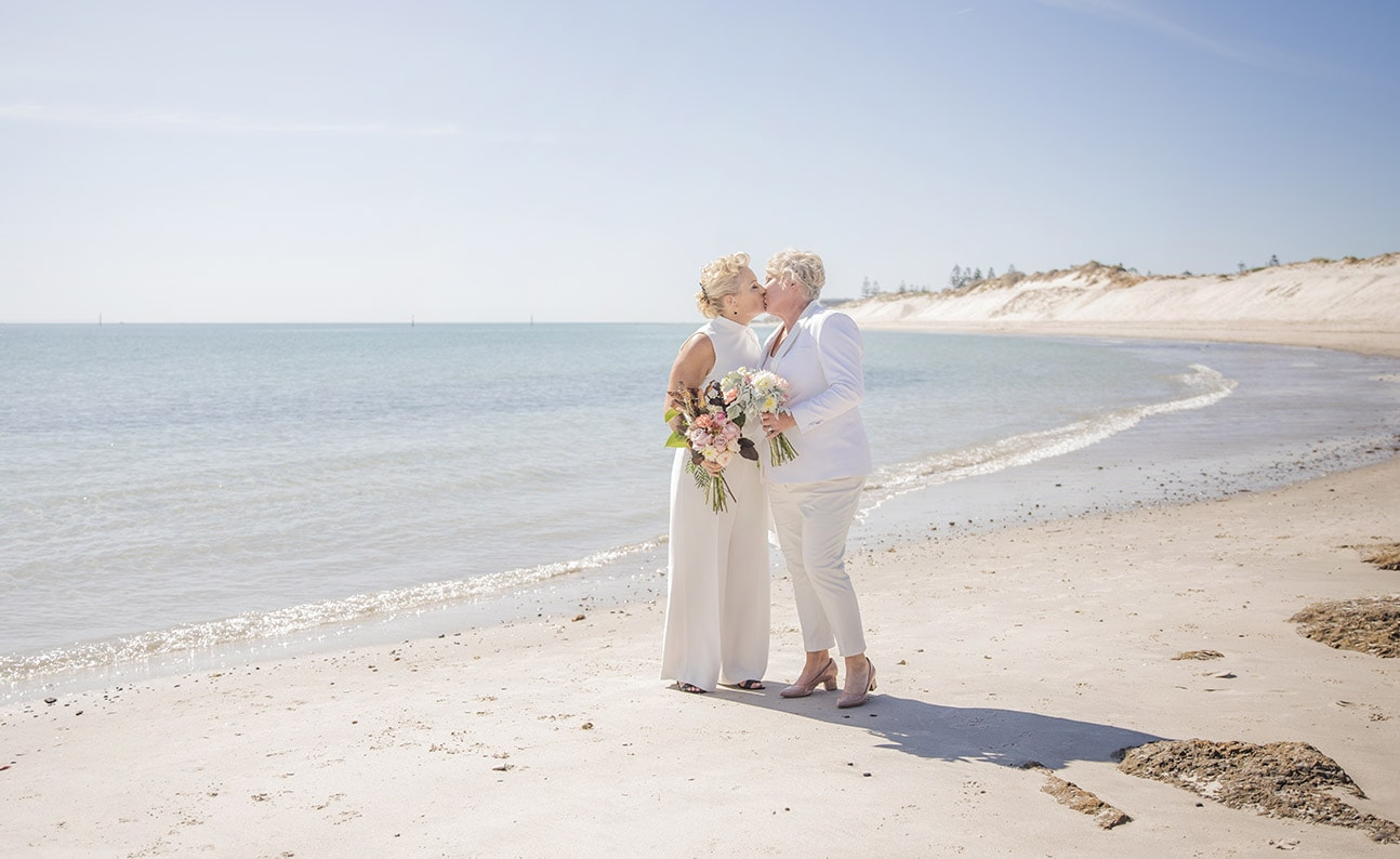 The two brides together on the beach