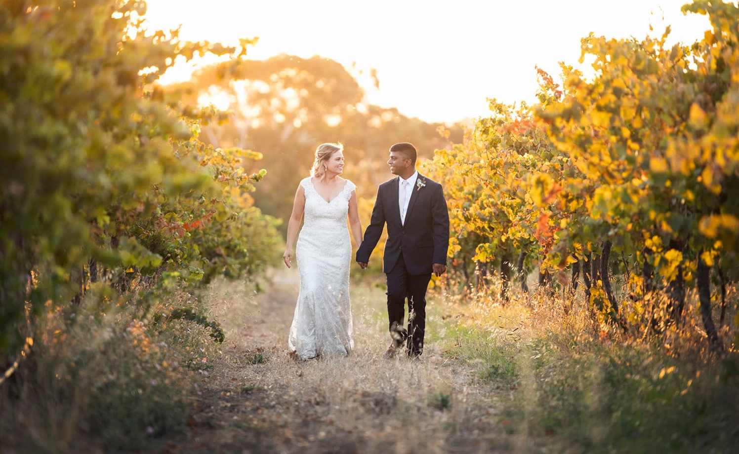 Bride and groom walking together in vineyards