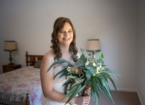 Bride holding bouquet as she gets ready