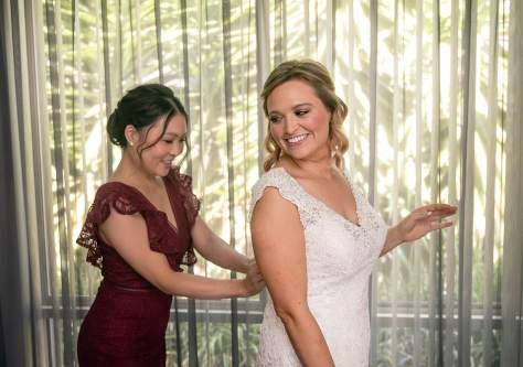 bridesmaid helping put on dress