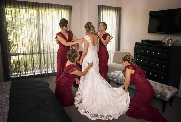 Bridesmaids fussing over bride