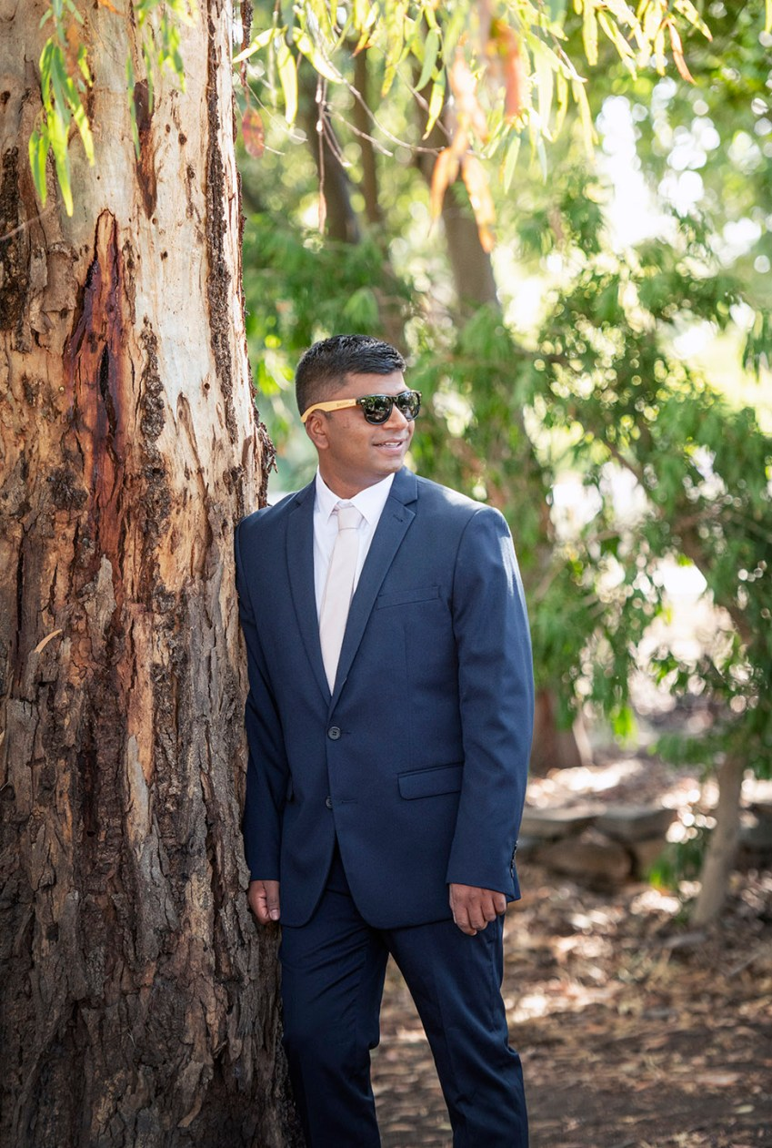 Groom leaning on tree