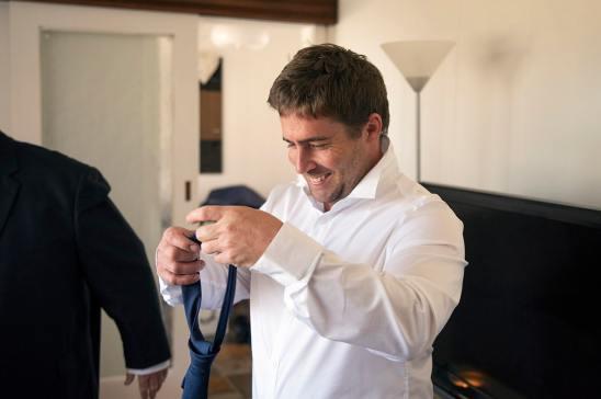 Groom putting on tie