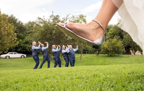 Bride stepping on groomsmen