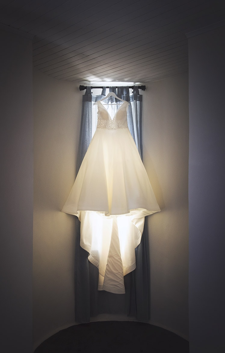 Wedding dress hanging illuminated by window