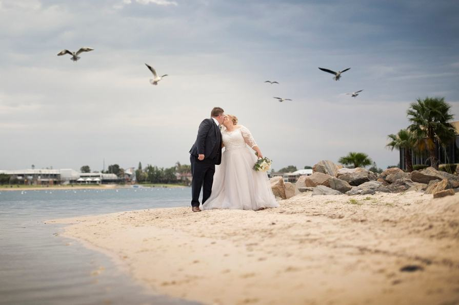 Sharing a kiss under seagulls