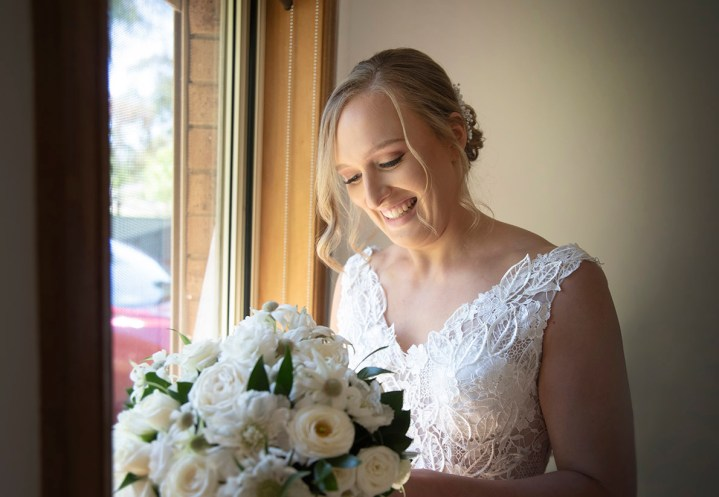 Bride looking at bouquet