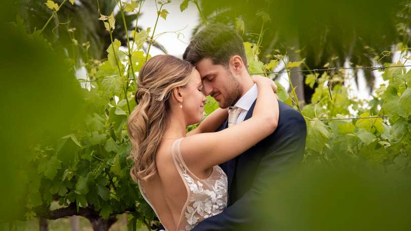 Bride and grom holding one another in vineyards 5