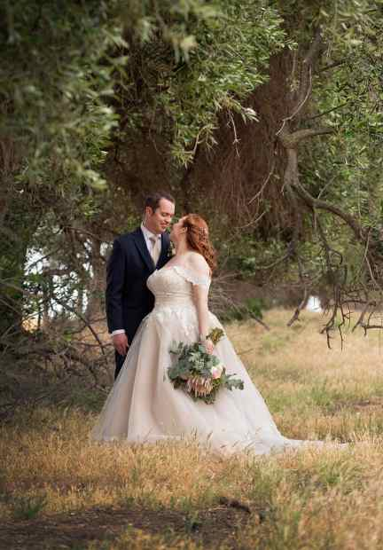 Bride and groom under gum trees
