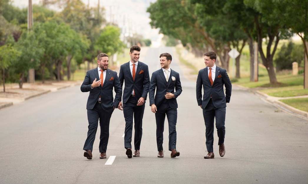 Groom and grooms men walking down road