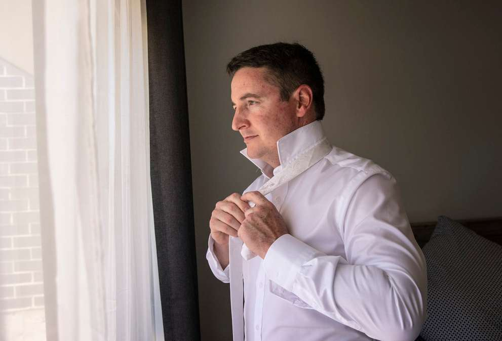 Groom putting on tie in front of window