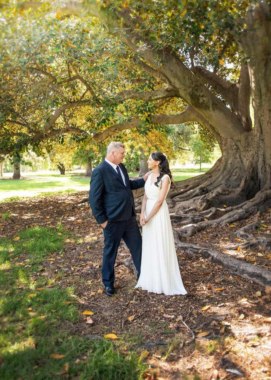 bride and groom standing under tree during their wedding ceremony