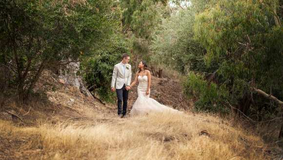 Bride and groom waling in long grass in bushland