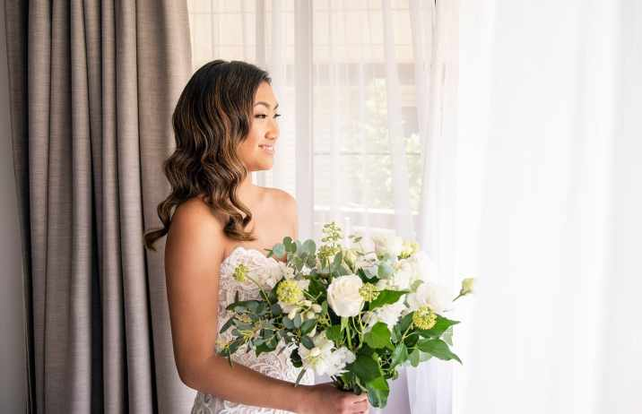 Bride looking out window with bouquet