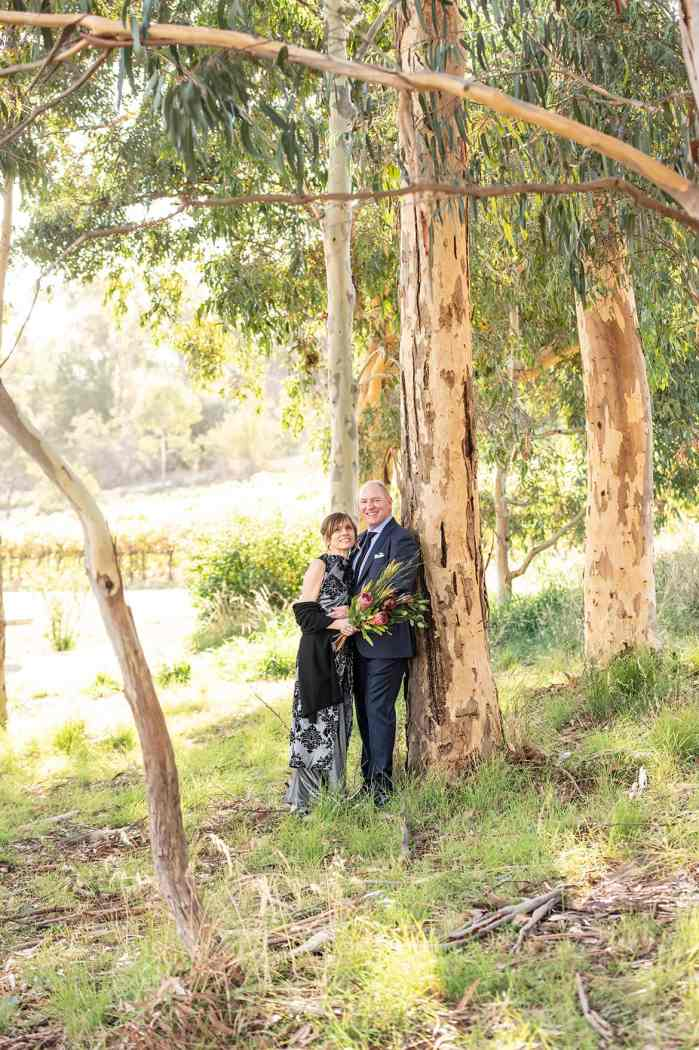 newly weds leaning against a tree together