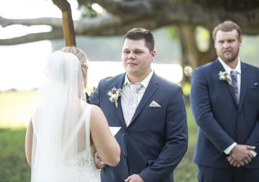 Groom listening to his bride's vows