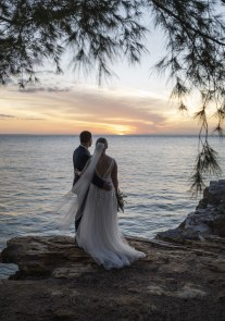 wedding couple looking out at the sunset