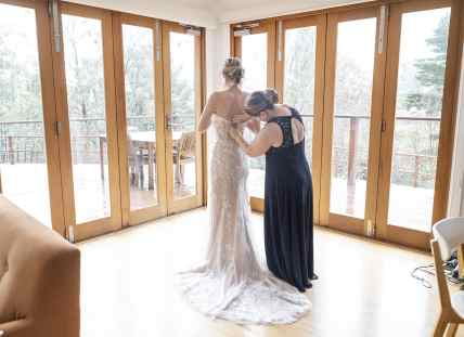Helping put on bridal gown