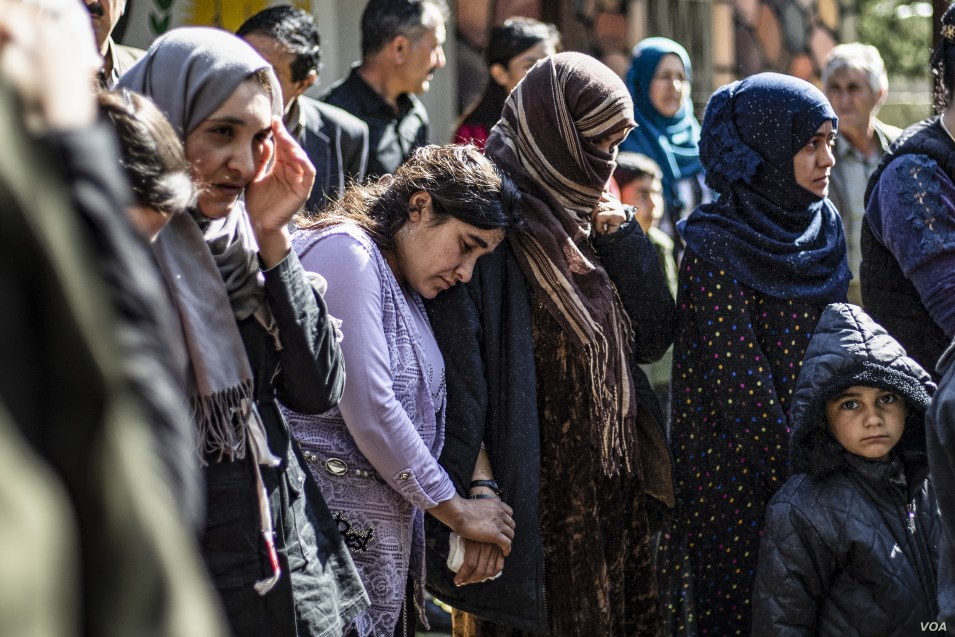 FILE - Iraqi Yazidi women and children rescued from the Islamic State group wait to board buses bound for Sinjar in Iraq's Yazidi heartland, April 13, 2019.