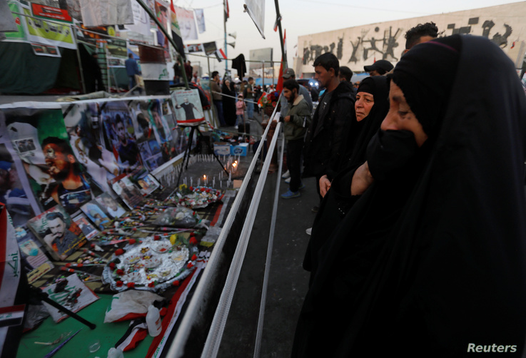 An Iraqi woman reacts as she looks at a makeshift memorial with personal belongings of those who were killed at an anti…