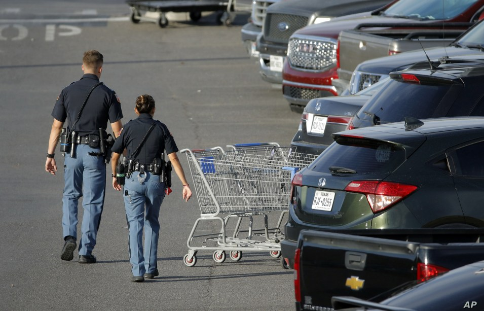 Police officers walk by shopping carts at the scene of a mass shooting at a shopping complex, Aug. 4, 2019, in El Paso, Texas.