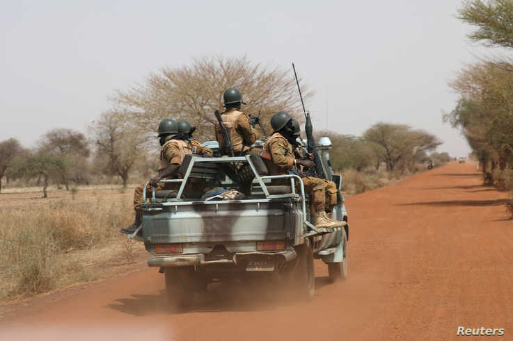 FILE - Burkina Faso soldiers patrol on a road in the Sahel area of Burkina Faso, March 3, 2019.