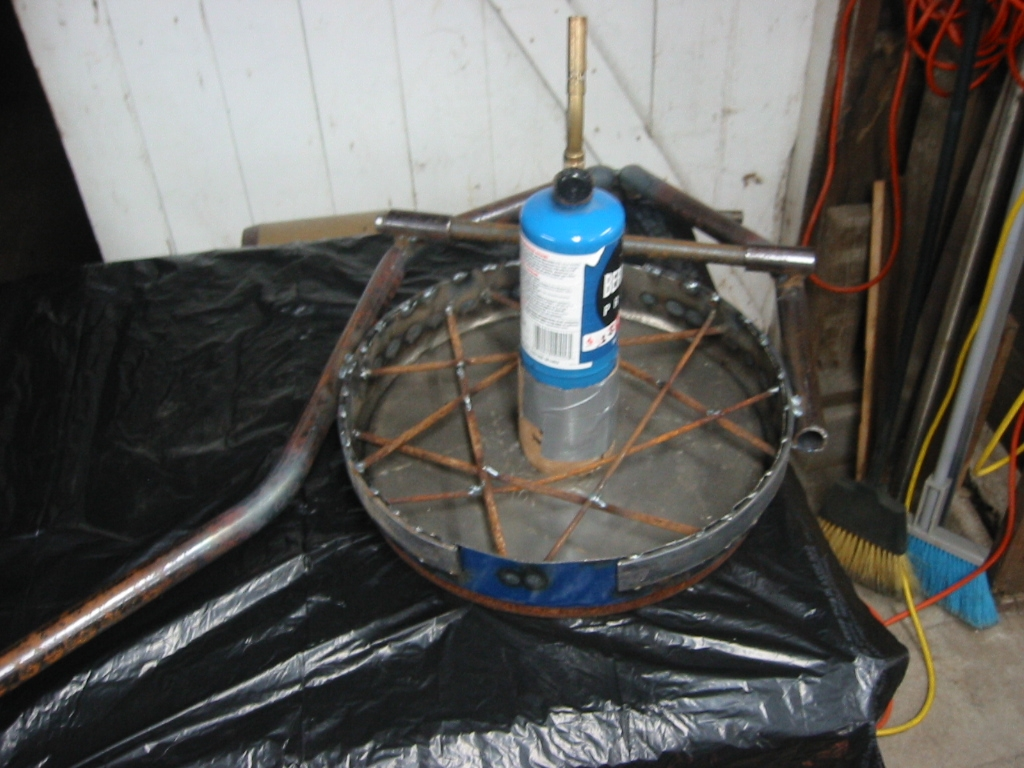 (2) Pipe frame welded to the top of the oil drum lid with rods to reinforce the Mizzou and a bottle to form the vent.