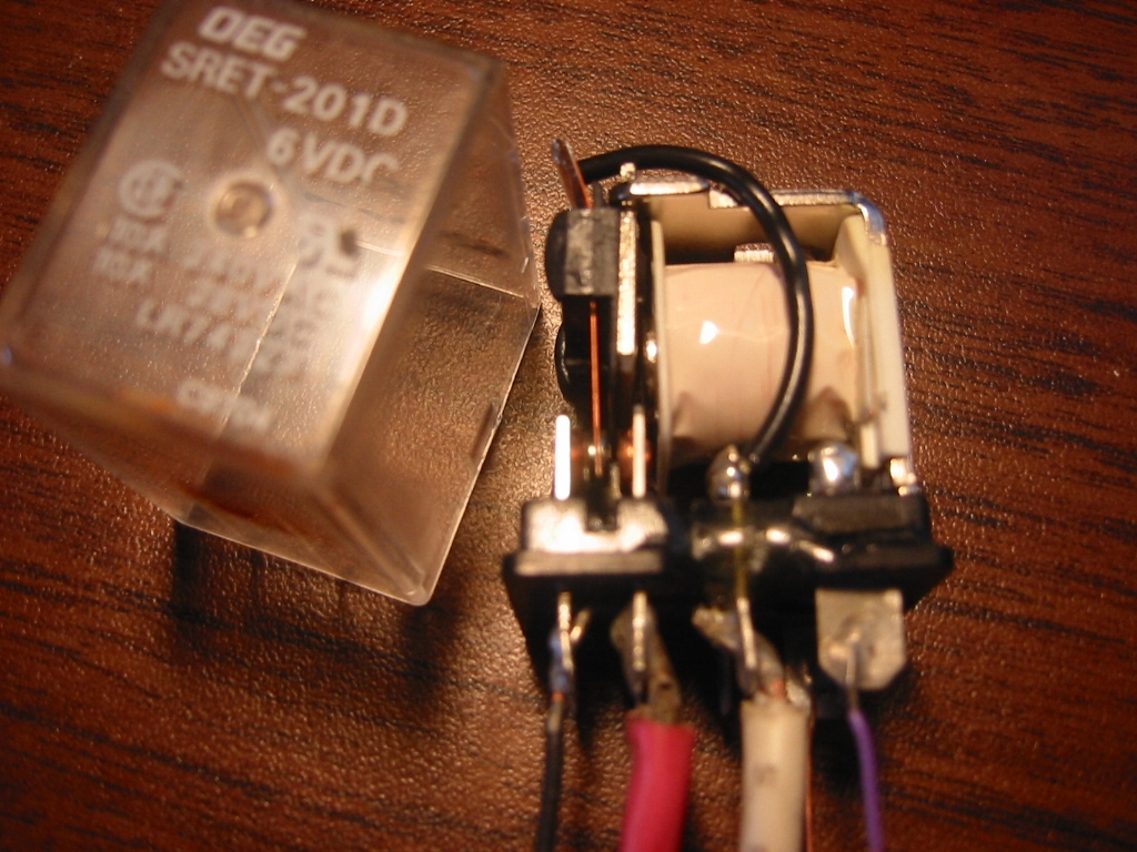 DPDT Relay with the cover removed showing the magnetic coil wrapped in white plastic and the contacts on the left side.