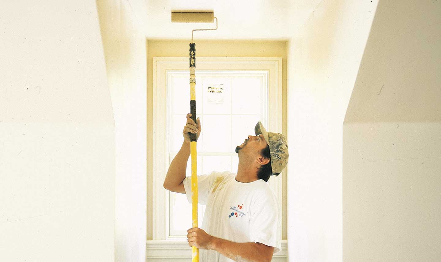 image of commercial painter rolling a drywall ceiling