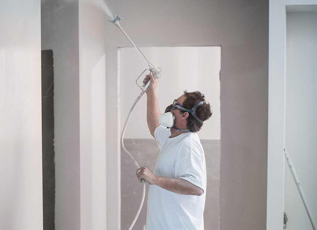paint contractor operating spray equipment and wearing safety eyewear and a respirator