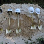 Six shovels stand upright in a pile of dirt, each with a construction hat perched on its handle.