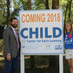 "Dorothy Thomas stands with a community partner next to a sign that reads, ""Coming 2018: CHILD Center for Early Learning."""