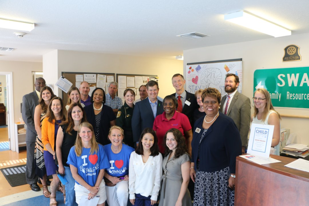 A large group of community partners post together inside the SWAG Family Resource Center.