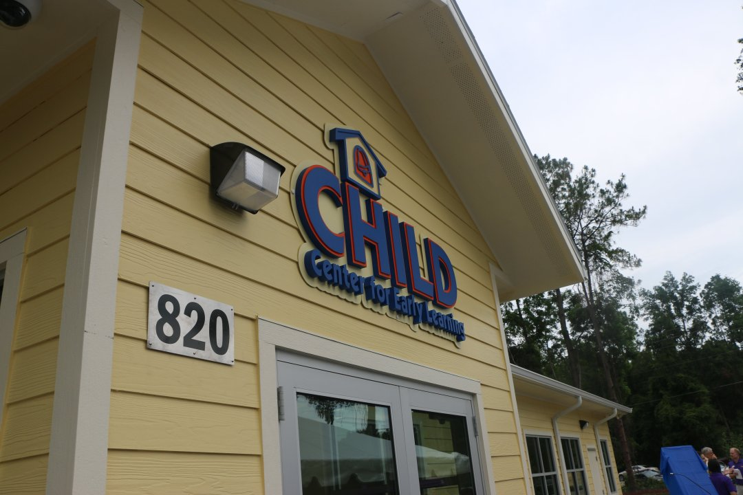 The front entrance of the CHILD Center, soft yellow with a blue logo over the door.