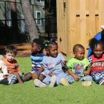 CHILD Center staff sit outside with a group of young children.