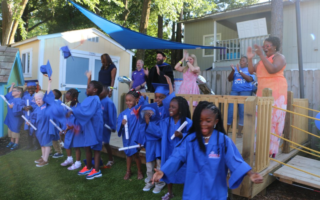 The first graduating class of the CHILD Center celebrates in blue graduation regalia.