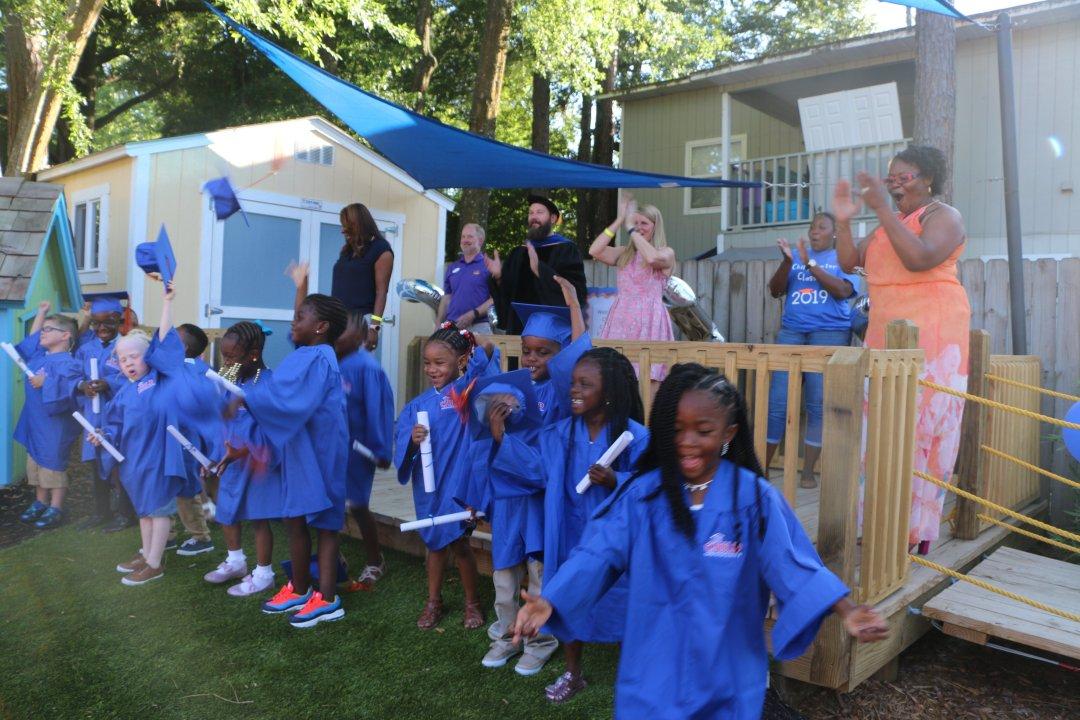The first graduating class of the CHILD Center celebrates in blue graduation regalia.