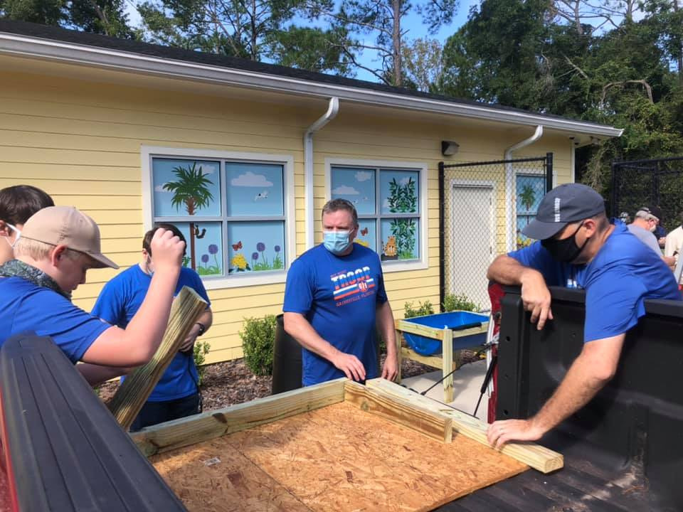 A team of Boy Scouts works together to build raised garden beds behind the CHILD Center